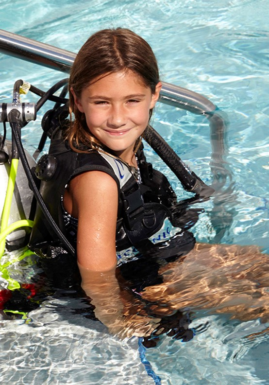 Resort lifestyle photo of little girl in the pool enjoying scuba diving lessons
